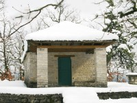 Snow covered traditional stone chapel in the forest around the village of Dilofo