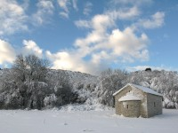 Snow covered traditional stone chapel in the stone village of Kato Pedina, close to the villages of Aristi and Elafotopos