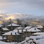 The snow has set on the tilled roofs of an old village in the mountains of Epirus