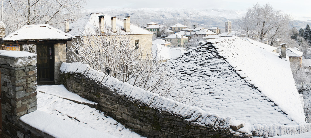 Snow covered roofs in a traditional stone village in the Zagori region, Greece