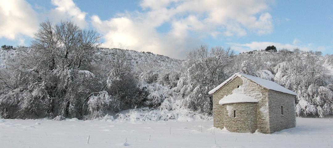 Snow covered church in Kato Pedina traditional stone village in the Zagori region in Greece