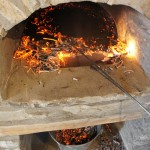The wood fired oven is almost ready to bake the bread, ashes are removed and the oven floor cleaned