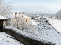 The first snow of the winter on the roofs of the stone houses in Dilofo village in Zagori below the mountain Tymfi