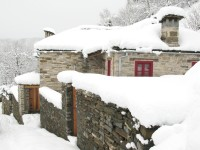 Snow covered trek by a two century old stone house in the Zagori, Epirus region