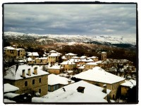 Snow has fallen on the roofs of the traditional stone houses of the village in Zagori