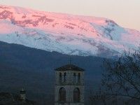 Subtle pink colours on the snow white mountain top in front of the village