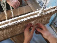 Four hands better than two in setting up the traditional loom
