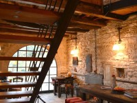 The main sitting area and the staircase to the upper level where the kitchen is with the traditional clay wood oven and the wood stove