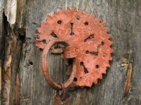 Rusty iron hoop fixed on a decorative rosette on a beaten old door in the village of Dilofo in Central Zagori
