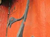 Traditional forged iron door knocker with a shape of a bird on a red wooden door in the stone village of Vradeto in Pindus National Park