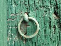 Rusty iron hoop on a woodworm eaten old door in the village of Tsepelovo in Central Zagori