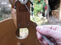The spinning frame puts the actual twist on the roving and turns it into yarn. This is collected on wooden bobbins