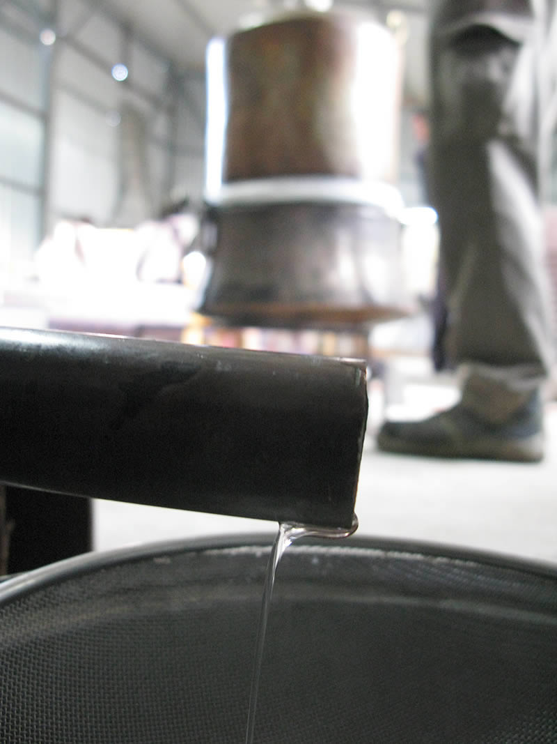 The water chills and condenses the vapors back into liquid, in this case mostly of alcohol. The alcohol is removed through a spout attached to the end of the worm