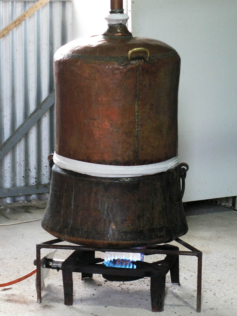 Vapors containing alcohol and some of the water rise up to the head, a cap on the top of the pot that captures the rising steam; the steam is drawn off into a tube called a lyne arm. Traditional distillation of tsipouro in Epirus, Greece