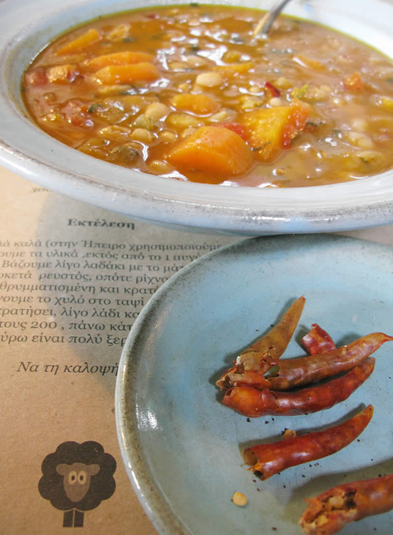A bowl of delicious traditional Greek bean soup accompanied by chili peppers. A typical plate up in the mountains of Pindus for the guests of the hotels and taverns