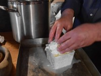 The artisan cheese is carefully transferred to the hoop where it will be allowed to drain from the curd by gravity, most likely overnight... at Anemi cafe in Central Zagori, Epirus