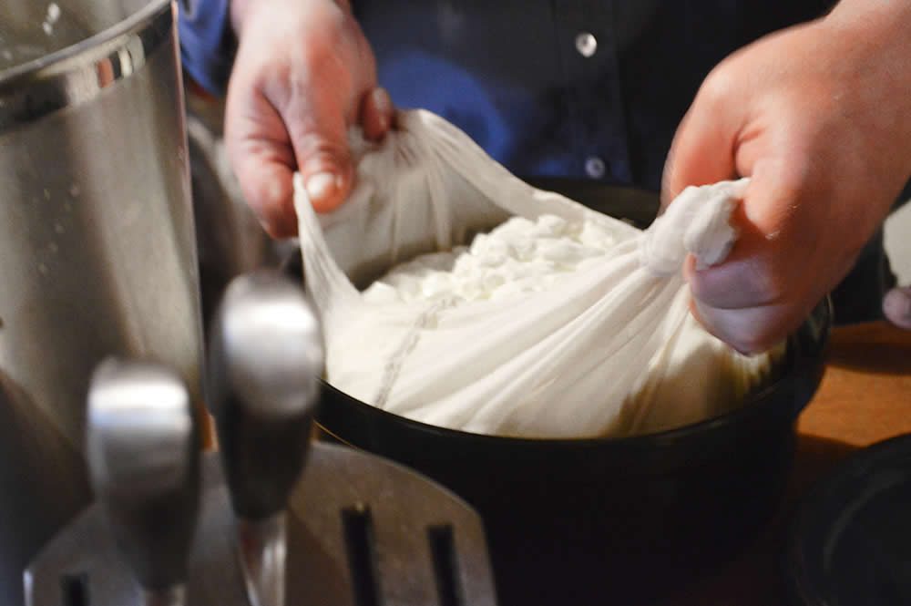 The fresh cheese curd is drained by hand at the artisan cheese making seminar in Zagori