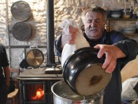 The experienced cheesemaker, aka Paparounas, removes most of the water (whey) from the cheese milk, and hence cheese curd to ensure the good quality of the cheese during the cheese making day in Anemi Guesthouse in Soudena