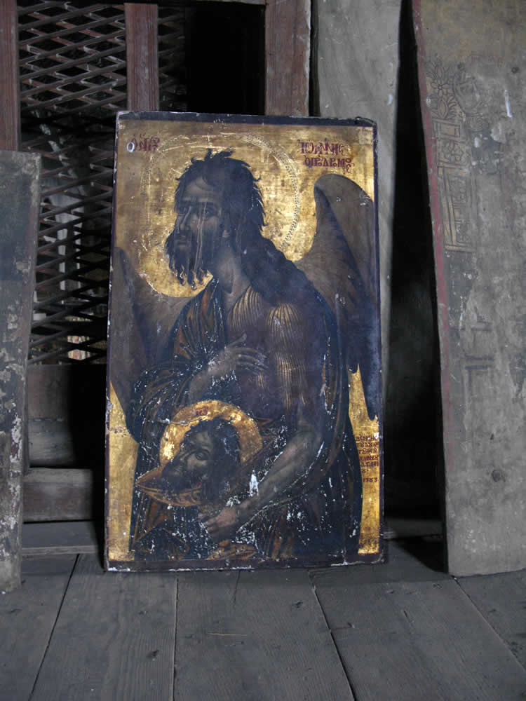 Gold trimmed painting of John the Baptist lying on the second floor of the gynaeceum of St. Georges triune church in Negades village, Zagorohoria