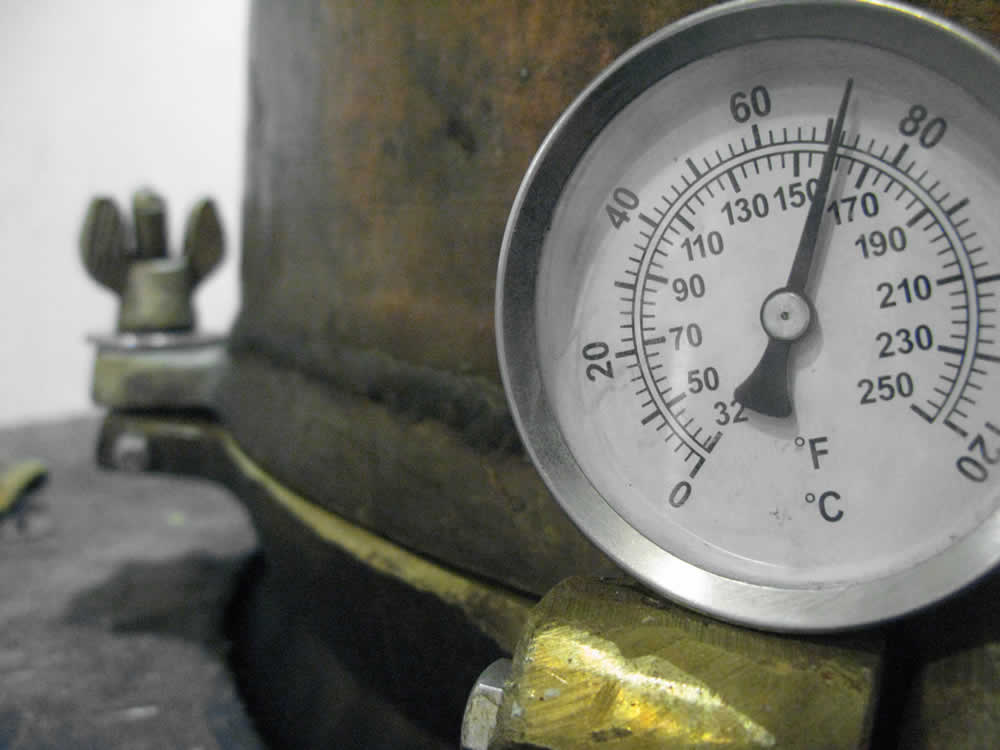 """Heating up the still with fire which is fed with logs manually by George the """"Master"""" distiller..."""