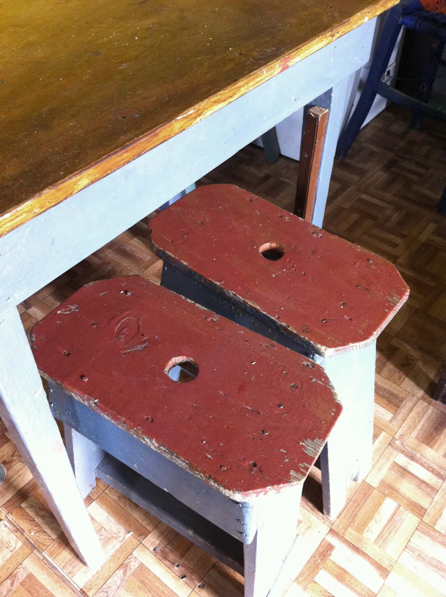 two stools, painted at least a dozen times through the life span of the kafeneion, waiting to be sat on in this traditional cafe in elafotopos, zagori, greece