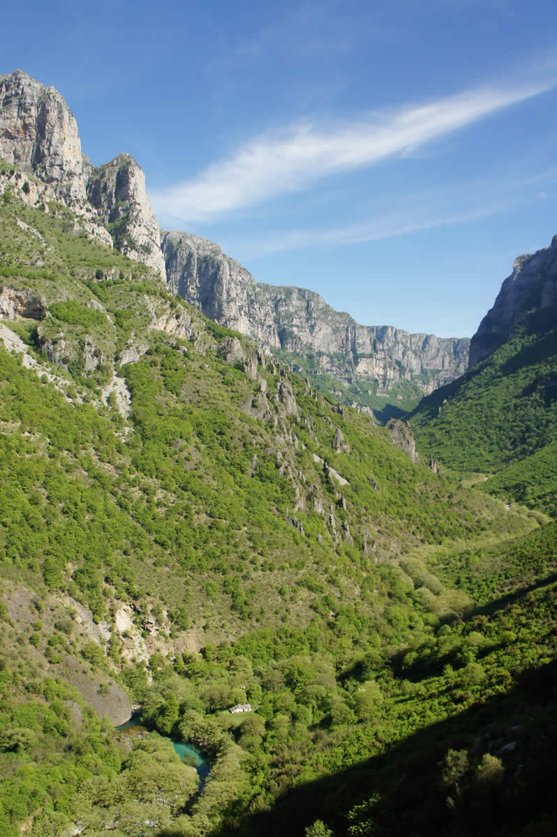 Vikos gorge as seen from the village Vikos. The springs of Voidomatis river and the nearby chapel of Virgin Mary can be seen at the bottom of the image